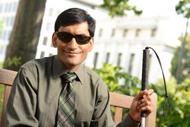 Image of man who is blind. He is wearing dark glasses and holding a cane while sitting on a bench.