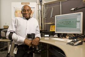 Image of man in a cubicle with a computer screen in the background. The man is holding crutches.