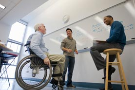 Image of three men talking and smiling in front of a whiteboard in a classroom. One of the men is in a wheelchair.