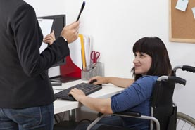 Image of two female co-workers talking in an office. One of the women is in a wheelchair.