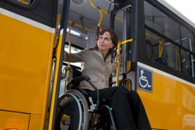 Image of woman getting off of a bus using a wheelchair lift.